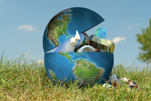 Earth globe in grass filled with assorted trash - concept representing environmental contamination of our planet by people and industry